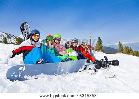 Team with snowboards and goggles sitting in a row