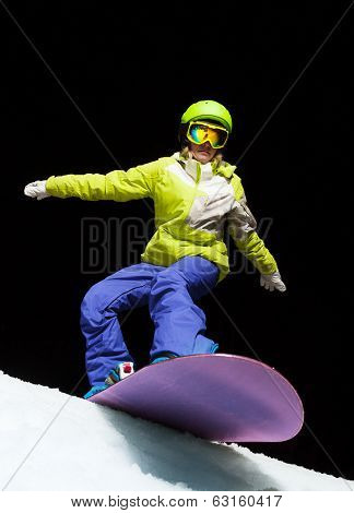 Girl ready to slide with snowboard at night