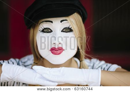 mime with black hat on the red background