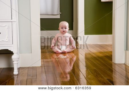 Chubby seven month old baby at home sitting on floor