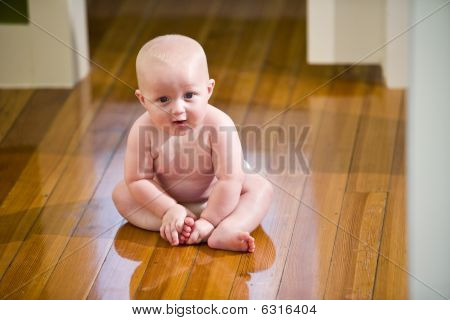 Cute chubby baby wearing diaper sitting on floor
