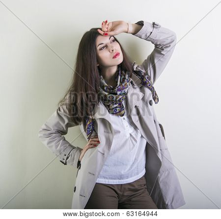 Beautiful young woman posing in a light raincoat.