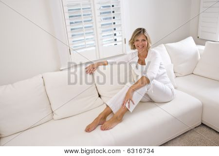 Woman relaxing at home on white couch
