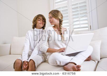 Niños sentados en casa en sofá blanco usando laptop