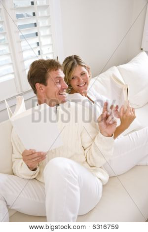 Couple relaxing together reading at home on white couch