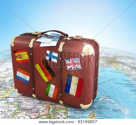 Old Suitcase With Air Ticket And Striples Flags On Blurred World Map And Sky In Background