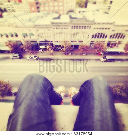 legs hanging over a tall building done with a retro vintage instagram filter