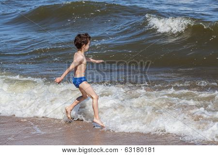 Little Boy Playing At The Seaside