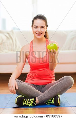 healt, dieting, home and happiness concept - smiling sporty teenage girl with green apple at home