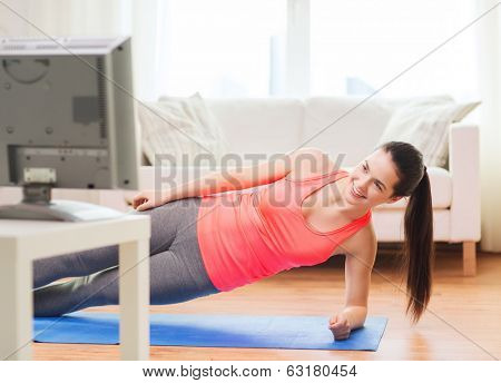 fitness, home and diet concept - smiling teenage girl doing side plank and watching tv at home