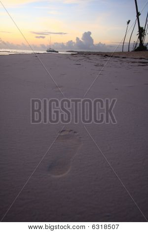 Footprints in sand at sunrise