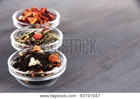Aromatic dry tea in bowls on wooden background