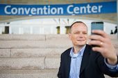 stock photo of selfie  - Business man taking a selfie with his smart phone in front of a convention center - JPG