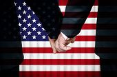 image of homosexual  - Two gay men stand hand in hand before a marriage altar featuring an overlay of the flag of the United States of America - JPG