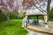 stock photo of gazebo  - Backyard of residential house in spring with wooden deck and gazebo - JPG
