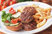 Spicy mini burgers served with french fries and salad