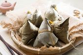 Asian Chinese rice dumplings on basket, tea at background.