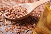 foto of flax plant  - Flax seed in a wooden spoon and a bottle with oil - JPG