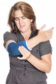 Woman with an injured painful arm elbow wearing a therapeutic elastic support band isolated on white