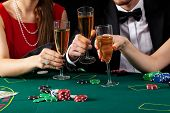 foto of champagne color  - Casino players proposing a toast with a glass of champagne - JPG
