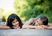 foto of hopscotch  - Two sisters laughing and playing with chalks on pavement in green sunny park - JPG