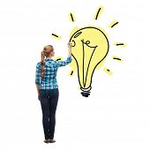 education and advertising concept - young woman from the back drawing light bulb in the air