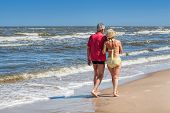 pic of stroll  - Mature couple strolling together at sandy coastline - JPG