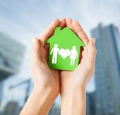 real estate and family home concept - closeup picture of female hands holding green paper house with