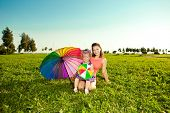 Beautiful little girl with mother rainbow umbrella holding  in  the park. Smiling child and mom on a