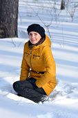 stock photo of beret  - Woman in beret and jacket sitting in the snow - JPG
