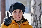 foto of beret  - Portrait of a woman in a black beret and yellow jacket showing a finger - JPG