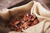 stock photo of pecan  - Pecans in Linen and Wooden Crate Closeup - JPG
