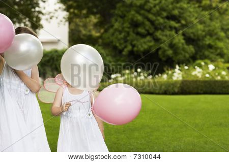 Two Young Girls In Garden, Wearing White Dresses, Holding Balloons