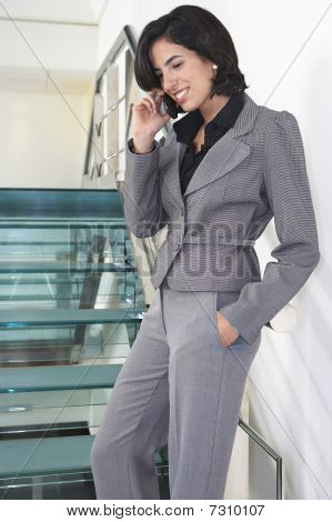 Young business woman standing in office corridor talking on mobile phone