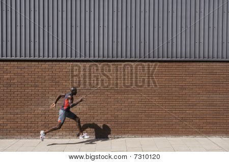 Man running past brick wall