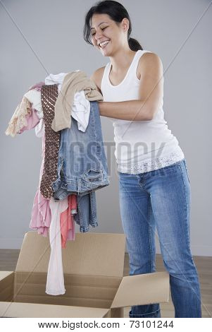 Young woman piling clothes into a cardboard box