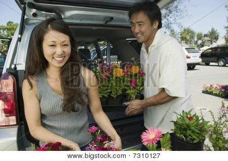 Woman With Husband  Loading Flowers Into Back Of Suv, Portrait