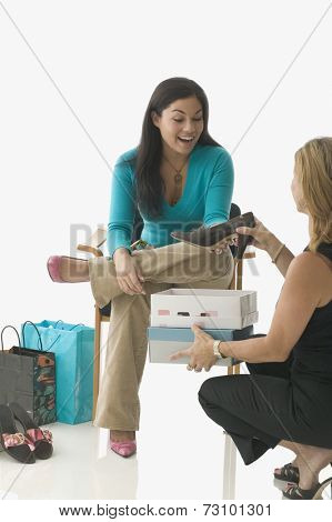 Sales clerk assisting teen girl buying shoes