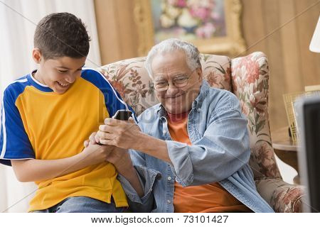 Young boy and his grandfather fighting over the remote control