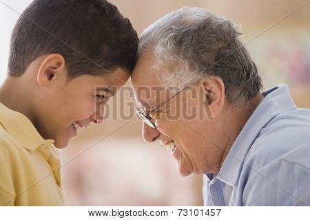 Older man touching foreheads with his grandson