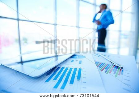 Business documents, touchpad and pen on background of businessman by office window