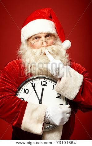Santa holding Christmas clock and making shhh gesture while looking at camera