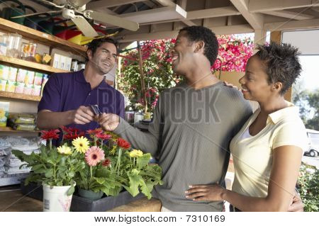 Couple purchasing plants in shop and paying by credit card