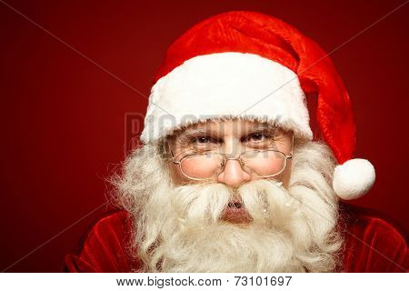 Head of positive Santa Claus in eyeglasses looking at camera