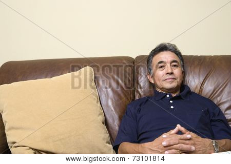 Portrait of senior man sitting on couch
