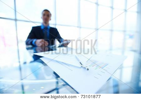 Financial documents and pen at workplace on background of businessman working