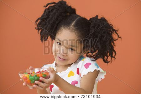 Portrait of Asian girl with ponytails holding bowl of candy