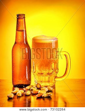 Bottle and glass full of beer with pistachio nuts on the table on yellow background, october beer fest, tasty alcoholic drink