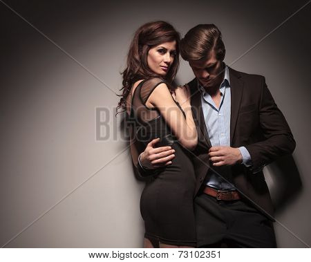 Side view of a elegant woman wearing a black dress embracing her boyfriend while he is leaning on the wall holding his jacket with one hand.