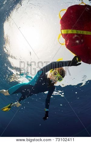 Young lady free diver relaxing on surface and holding the red buoy